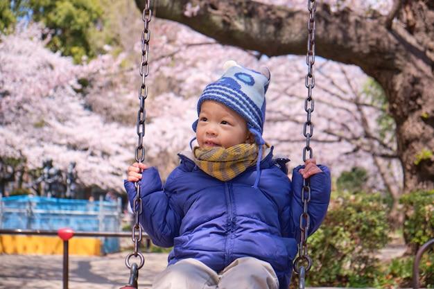 Милый маленький азиатский малыш 2–3 лет, весело проводящий время на качелях на детской площадке с цветами сакуры в токио, япония, весенний сезон
