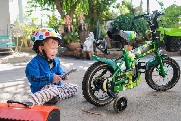 安全ヘルメットを身に着けているかわいい幸せな笑みを浮かべて小さなアジア2  -  3歳の幼児男の子子供