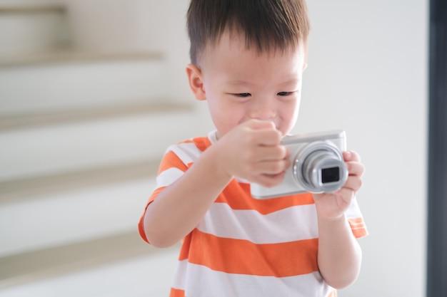 かわいい小さな笑顔アジア2-3歳の幼児男の子子供デジタルカメラを使用して写真を撮る