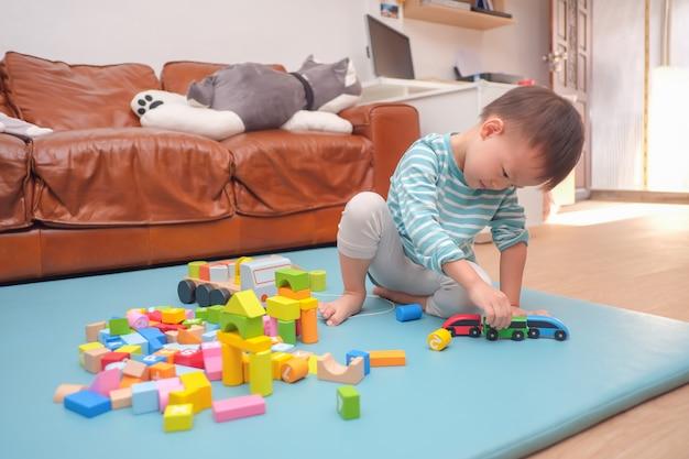 Азиатский малыш 2 - 3 лет, весело проводящий время, играя с игрушками из деревянных строительных блоков в помещении дома