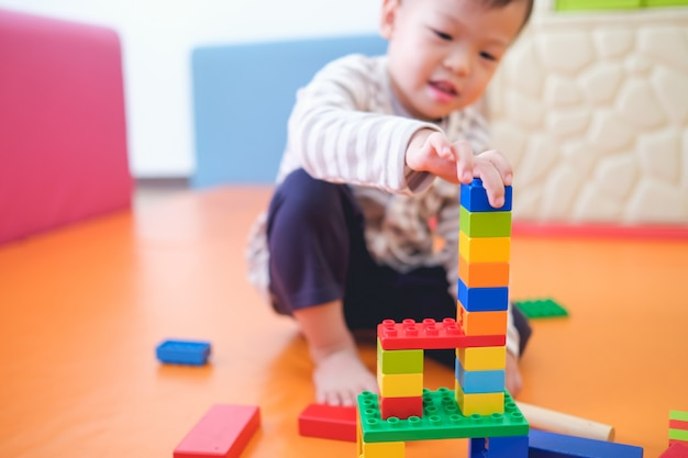 Милый маленький азиатский малыш 2–3 лет, весело проводящий время, играя с красочными пластиковыми блоками в помещении в игровой школе, детской, гостиной, образовательных игрушках для детей младшего возраста.