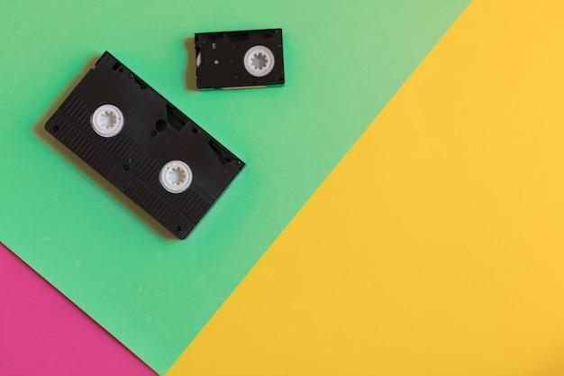 2つのレトロなビデオカセットオン3色紙の背景。