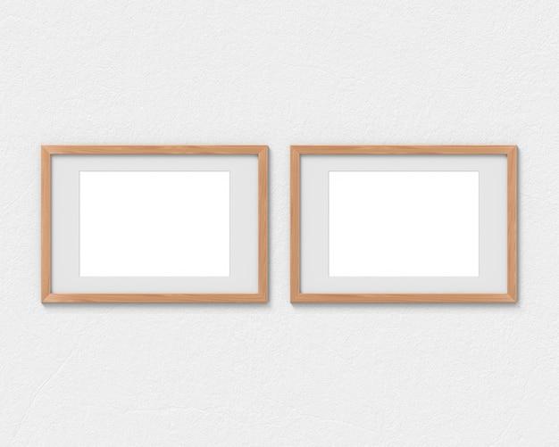 壁に掛かっている境界線を持つ2つの水平木製フレームモックアップのセット。画像またはテキストの空のベース。 3dレンダリング。
