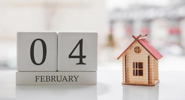 2月のカレンダーとおもちゃの家。月の4日目。印刷または記憶用のカードメッセージ