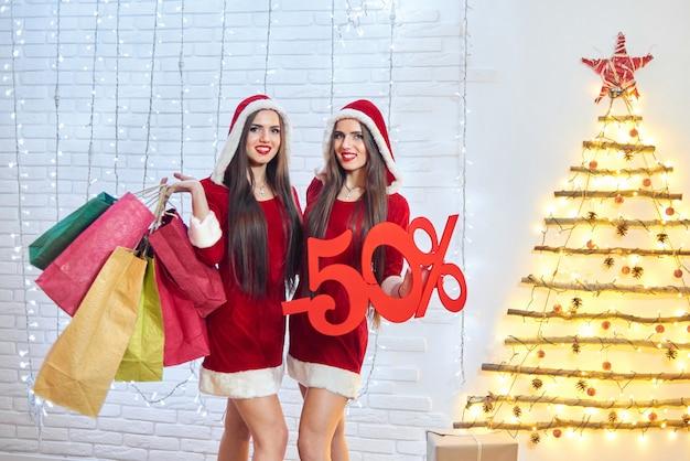 ショッピングバッグでポーズをとるクリスマス衣装の2人の幸せな若い雪の乙女の水平ショットと-50割引サインcopyspace消費者向け季節限定販売の買い物中毒のクリスマス。 2018年