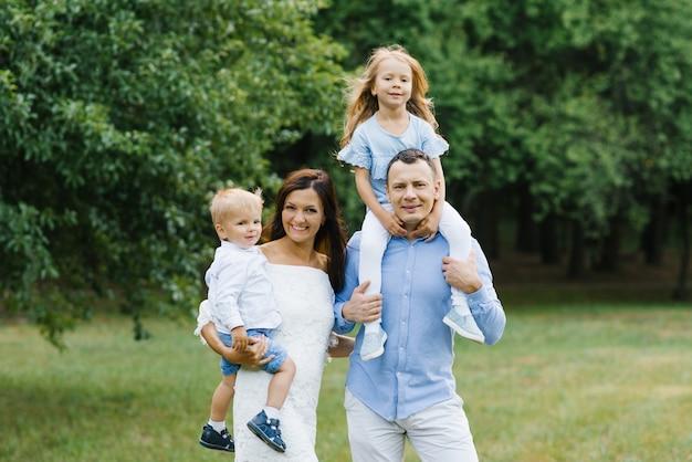 美しい家族の肖像:ママ、パパ、2歳の息子、5歳の娘。親は子供を腕に抱きます。