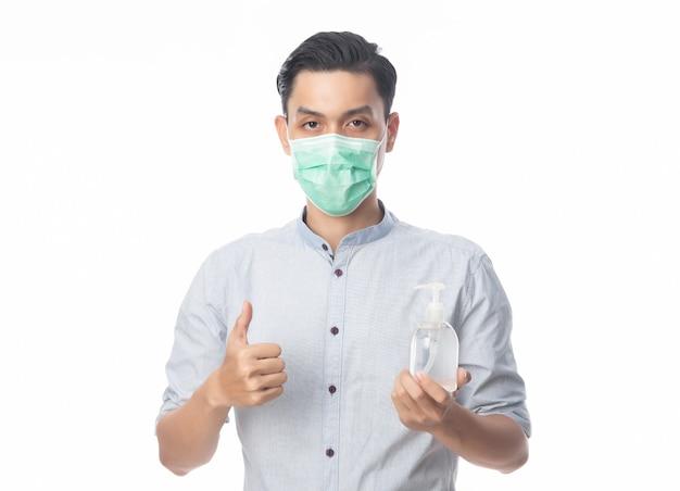 若いアジア系のビジネスマンは衛生的なマスクを着用し、ハンドシンチナイザーを持ち、感染を防ぎ、コロナウイルス。午後2.5戦闘などの空中呼吸器疾患と白で隔離されるインフルエンザ。