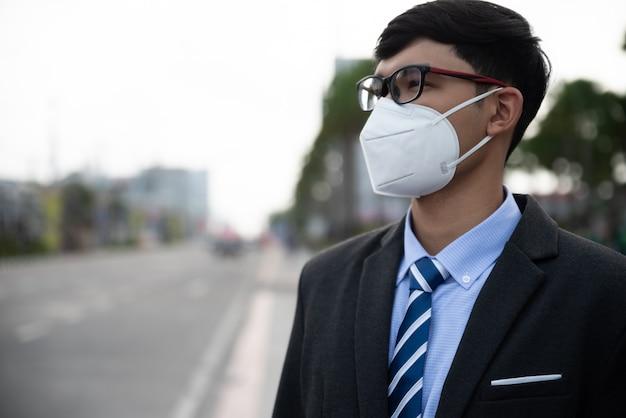 保護フェイスマスクと咳、コロナウイルスと午後2.5の戦いを着ているビジネスマン