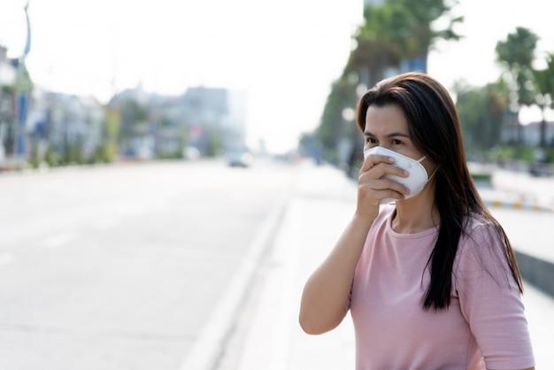 Женщина, носящая защитную маску и кашель, для лечения коронавируса и вечера 2,5