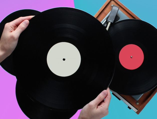 ビニールレコード、2色の背景上のレコードを持つビニールプレーヤーを保持している女性の手。レトロなスタイル、80年代、トップビュー