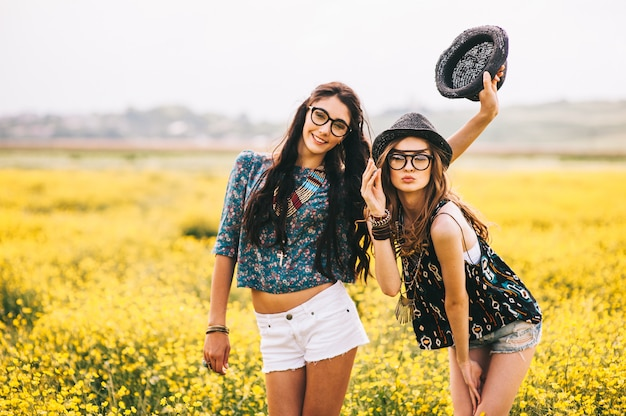 2 beautiful hippie girl in a field of yellow flowers