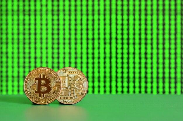 2つの金bitcoinがディスプレイの背景に緑色の面にあります