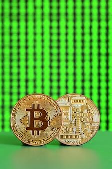 2つの金bitcoinが緑色の表面にあります