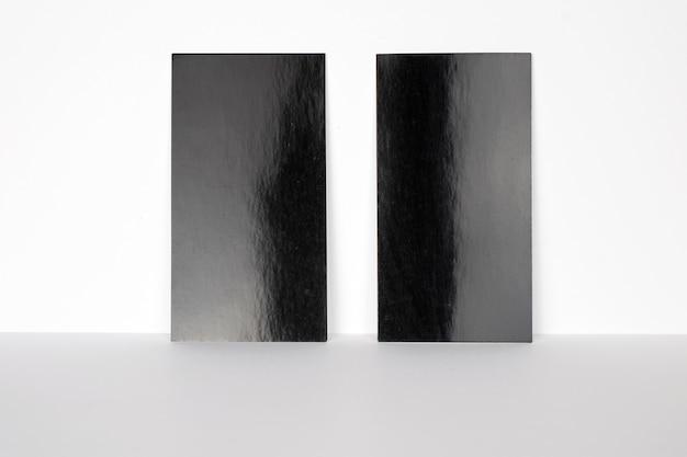 흰 벽에 고정 된 2 개의 빈 검은 색 명함, 3.5 x 2 인치 크기