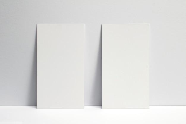 흰 벽에 고정 된 2 개의 빈 명함, 3.5 x 2 인치 크기