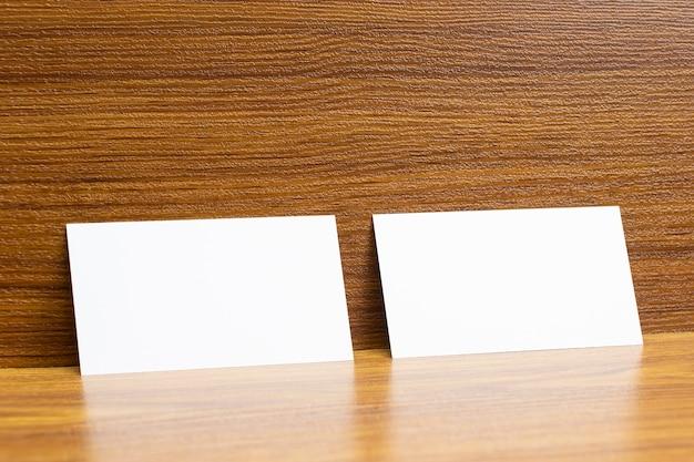 나무 질감의 책상에 고정 된 2 개의 빈 명함, 3.5 x 2 인치 크기