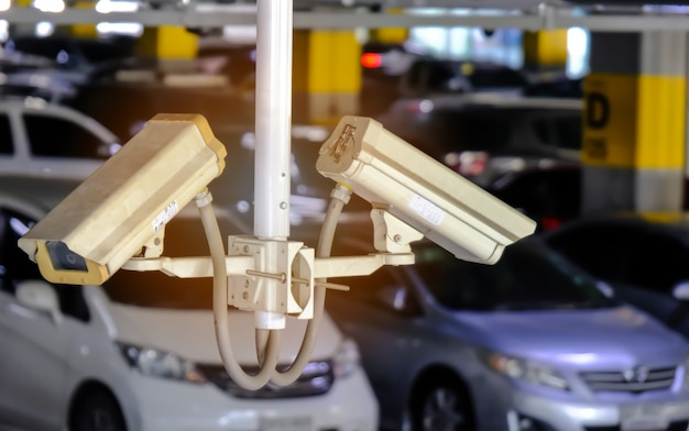 2 cctv or close circuit television are monitor and record cars in parking lot of shopping mall