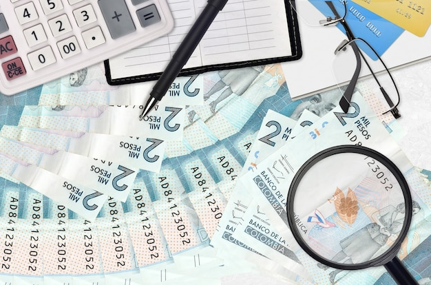 2 банкноты колумбийских песо и калькулятор с очками и ручкой. концепция сезона уплаты налогов или инвестиционные решения. ищу работу с высоким заработком