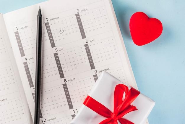 バレンタインの日グリーティングカード。水色の2月カレンダー上のギフトボックスと赤いハート。挨拶トップビューのcopyspace