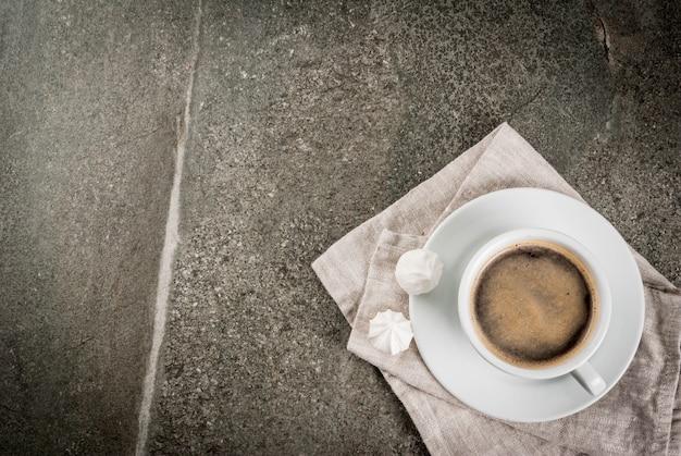コーヒーブレイク。朝ごはん。朝。コーヒーカップと石の暗いテーブルの上の2つのメレンゲ。トップビューcopyspace