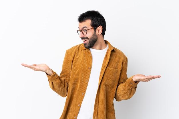2つの手でcopyspaceを保持している白でコーデュロイジャケットを着てひげと白人のハンサムな男
