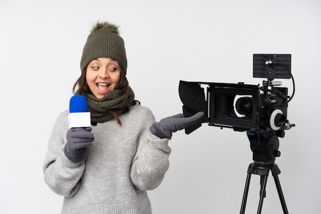マイクを保持していると2つの手でcopyspaceを保持している白い壁にニュースを報告するレポーター女性