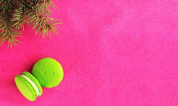 赤い紙の背景にフォンダンと2つの緑のマカロン。クリスマスツリーの枝の近く。フラット横たわっていた、copyspace。