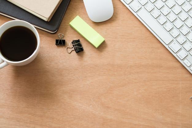 Коричневый деревянный рабочий стол с чашкой кофе, дневником, клавиатурой и 2 ножницами, вид сверху фон с copyspace