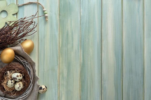 イースターフラットは、巣にウズラの卵と2つの黄金の卵、copyspaceと明るい緑の木製の板に横たわっていた