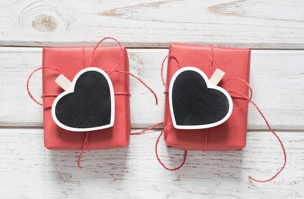 Валентинка. 2 красных подарочной коробки с зажимкой для белья как сердце с copyspace на доске на деревянном свете. вид сверху.
