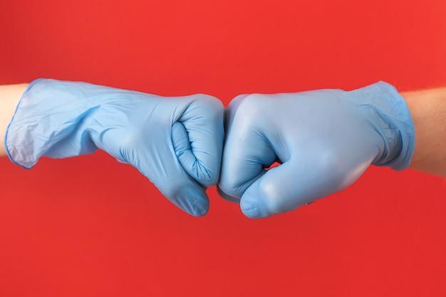 青い医療用手袋をはめた2つの手は、挨拶のように拳を握っています。ウイルス、パンデミック、伝染病、病気からの概念保護。ミニマリズム、copyspace。男性と女性の手。
