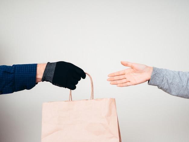 白い背景の上の紙袋を持つ2つの手。 covid-19パンデミックの配送コンセプト。