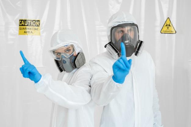 防護服を着た男性と女性の2人の医師が、手で注意のサインを見せています。コロナウイルスの流行の概念。 covid-19