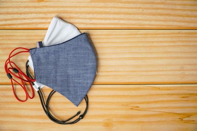 Взгляд сверху лицевого щитка гермошлема ткани 2 diy на деревянной таблице. защитите слюну, кашель, пыль, загрязнения (pm 2,5), вирусы, бактерии, коронавирус. handmade, diy концепция. копировать пространство