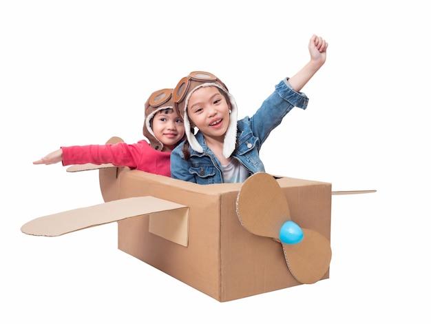 クリッピングパスと白で分離された段ボール飛行機を遊んでいるアジアの兄弟かわいい女の子。アジアの2人の子供が段ボール飛行機diyのパイロットとして遊びます。