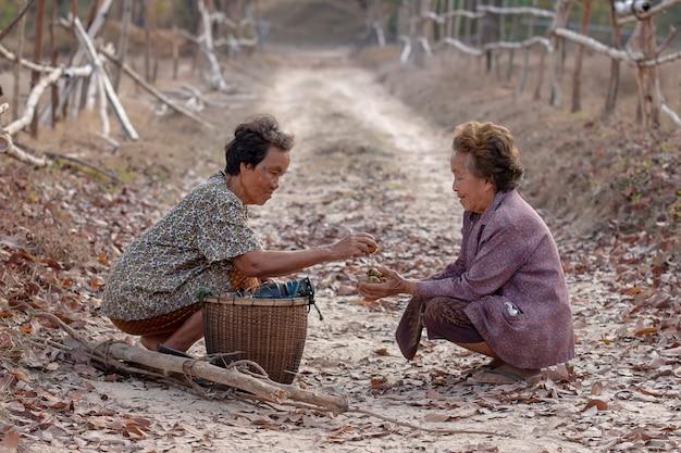 아시아의 노인 여성 2 명이 함께 행복을 전하고 있습니다.