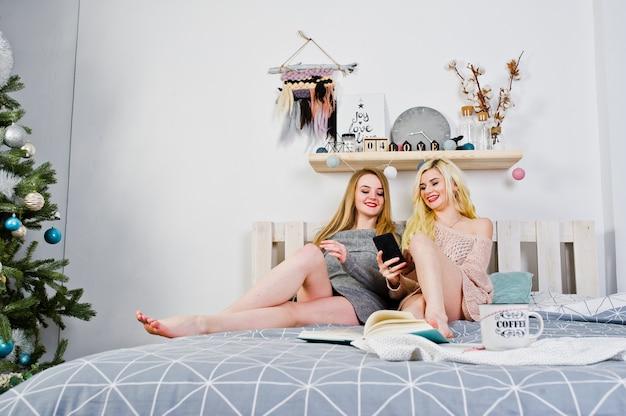 2つのeleganteブロンドの女の子は、ベッドの上に座って暖かいチュニックに着用します。