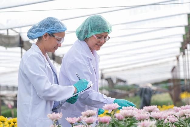 研究室のガウンと髪のカバーを持つ2人の科学者の女性は、花のビジネスの良い実験の概念とマルチカラーflowers.smilingの前に立っています。