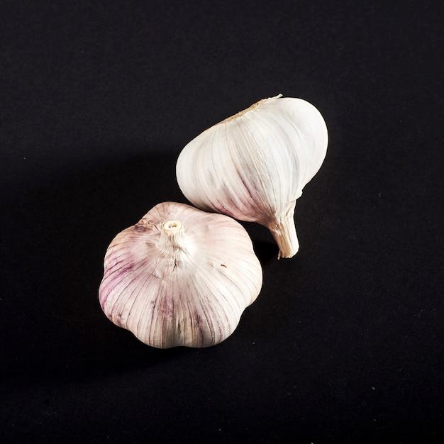 2 bulbi di aglio fresco su fondo nero