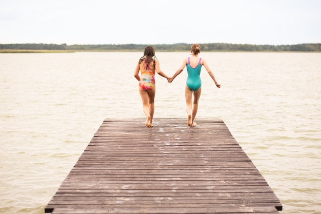2 girls on holiday running on wooden bridge to jump into water, rear view, summer time, vacations, holding hands