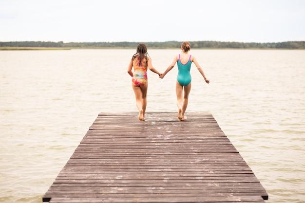 水に飛び込むために木製の橋を走っている休日の2人の女の子、背面図、夏の時間、休暇、手をつないで