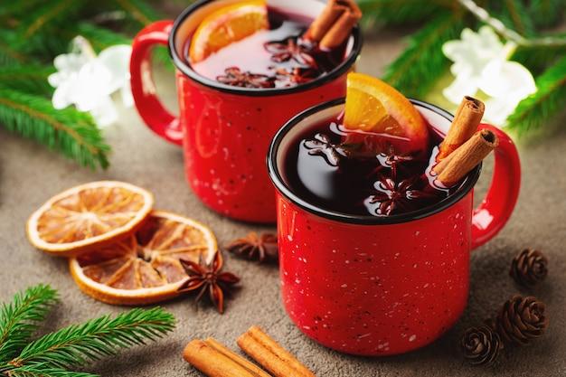 クリスマスホットワイン2杯または素朴なテーブルの上のスパイスとオレンジのスライスとgluhwein