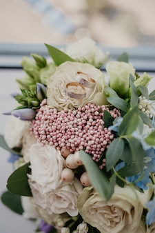 2 golden rings on wedding bouquet with beautiful roses