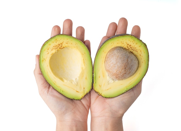 2 hand holding avocado cut in half isolated on a white background, the flesh of the avocado is creamy and soft with a buttery taste. avocados contain nutrients, vitamins and good fats.