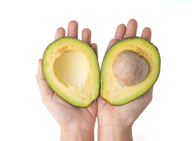 2 손을 잡고 아보카도를 반으로 잘라 흰색 배경에 고립, 아보카도의 살은 크림 같고 버터 맛이 부드럽습니다. 아보카도에는 영양소, 비타민 및 좋은 지방이 포함되어 있습니다.