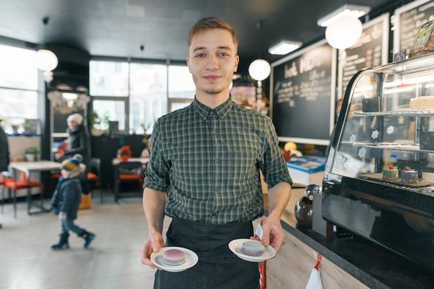 コーヒーショップで働く若い微笑の男は、マカロンと2枚のプレートをholdng。