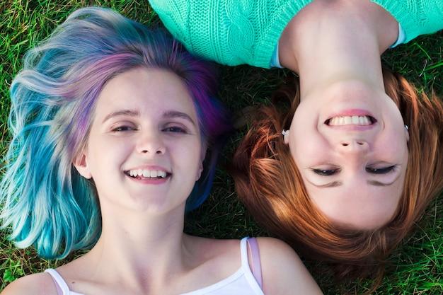 公園の芝生の上に横たわる2つの幸せな陽気な若いレズビアンの女の子。上面図。カラフルな髪、笑顔の友人とかなりティーンエイジャー。 lgbtの概念、素敵なレズビアンカップル屋外。美しい女性。