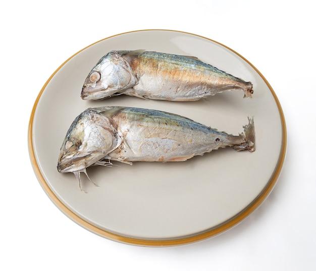 2 скумбрии на тарелке, изолированной на белом фоне. скумбрия - это небольшая рыба, которая популярна для приготовления пищи, мясо скумбрии имеет много питательных веществ. и линолевая, и кокозагециновая кислоты (dha).