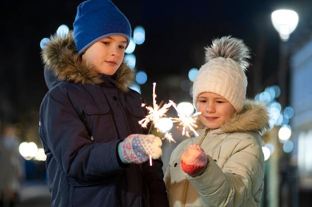 2 милых маленького ребенка, мальчик и девушка в теплой зимней одежде держа горящие фейерверки бенгальского огня на темной ноче outdoors. концепция празднования нового года и рождества.