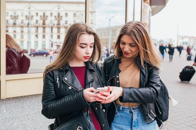 2 счастливых друз женщин деля социальные средства массовой информации в умном телефоне outdoors в городе. две молодые женщины разговаривают по мобильному телефону